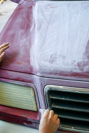 A close up view of a man's hand sanding the hood of a truck before a paint job