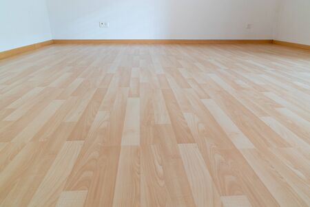 A low angle horizontal view of new wooden parquet flooring in a bright light and white apartment room