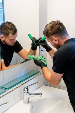 A professional cleaner scraping dirt and spots from a bathroom mirror during a general spring cleaning of an apartment bathroom