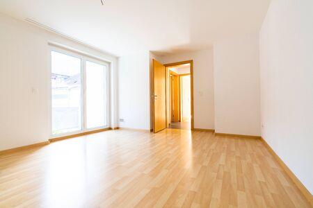 A low angle vertical view of new wooden parquet flooring in a bright light and white apartment room 免版税图像
