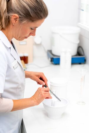 A blonde female pharmacist perparing a medical ointment in the laboratory of the pharmacy