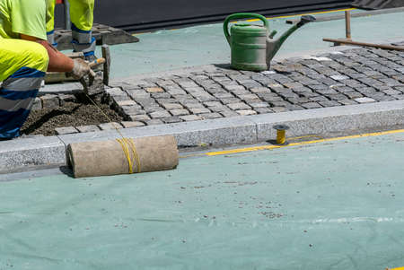 A close up view of a construction worker building a cobblestone sidewalk