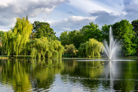 View of beautiful city gardens and park with a pond and geyser fountain