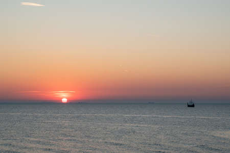 silhouette of an old Viking ship saling off into the sunset on the Baltic Sea