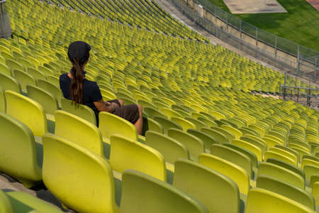 A single woman with long brown hair sitting alone in giant and empty stadium Stock Photo