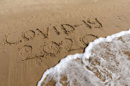 View of Covid-19 and 2020 text in sand on beach is covered by ocean wave and disappears Stock fotó