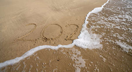 the year 2020 in tet written in sand on beach is covered by ocean wave and disappears