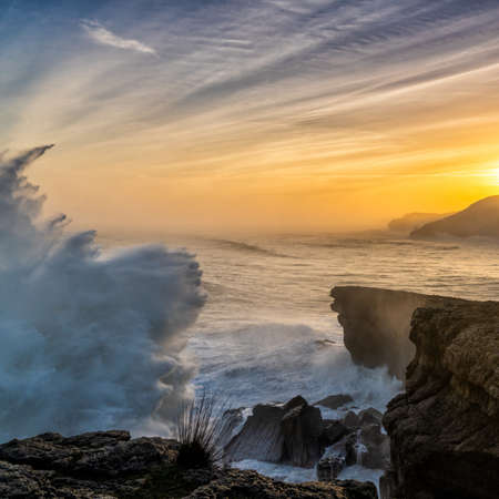 A view of huge storm surge ocean waves crashing onto shore and cliffs at sunrise