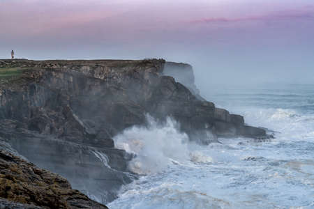 huge storm waves crash onto the Cape Ajo in Spain with the lighthouse on the cliffs above at sunrise Stockfoto