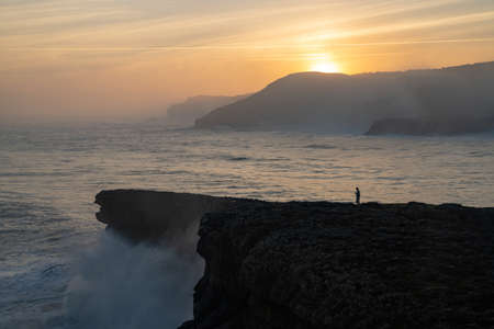 A view of huge storm surge ocean waves crashing onto shore and cliffs at sunrise with a person standing there