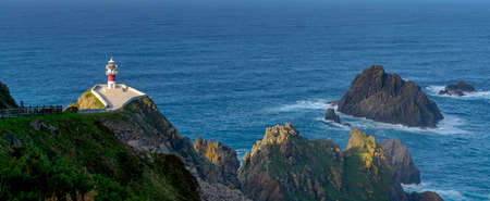 A panorama of the Cabo Ortegal lighthouse in Galicia with green cliffs and sunlight and deep blue ocean