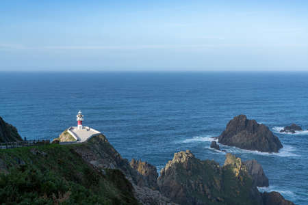 the Cabo Ortegal lighthouse in Galicia with green cliffs and sunlight and deep blue ocean Stok Fotoğraf