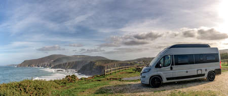 Panorama of a camper van parked high up on cliffs of a wild and rugged coastline