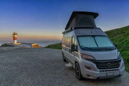 gray camper van parked at Cabo Ortegal lighthouse on the coast of Galicia at sunset