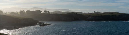 A panorama view of the misty and rocky tree-lined shore in Galicia