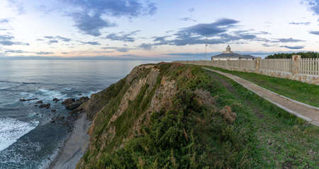 A view of the Cabo de Busto lighthouse at sunset