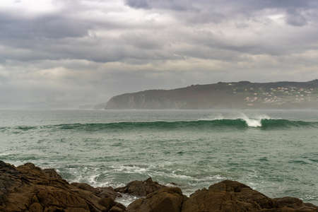 beautiful big waves breaking at surf spot Frouxeira beach in Galicia