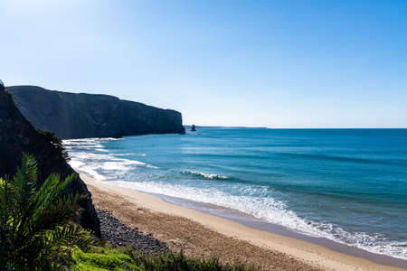 A view of the bay at Arrifana with ist golden beach and steep cliffs Stock fotó