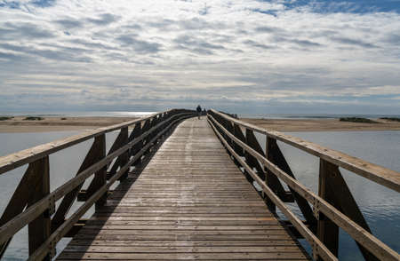 View of people crossing long wooden boardwalk to access La Gaviota Beach in Andalusia