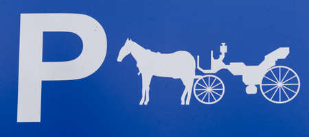 A close up detail of a parking lot sign exclusively reserved for horse and carriage