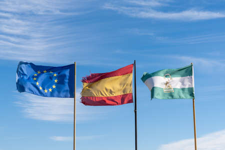 The flags of the European Union and Spain and Andalusia inder a blue sky with wispy clouds