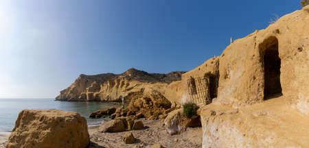 View of sandstone caves and dwellings with cliffs behind at an idyllic cove and beach on the coast o Murcia