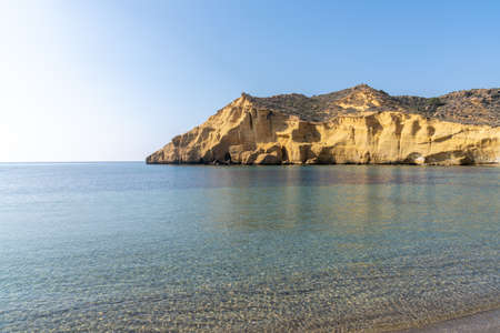 View of calm idyllic ocean water in the Mediterranean with yellow sandstone cliffs behind