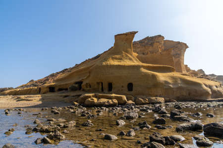 View of sandstone caves and dwellings at an idyllic cove and beach on the coast o Murcia