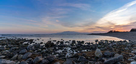 A panorama of a colorful sunset on the Mediterranean Sea in Almeria with rocks and tidal pools in the foreground