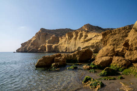 A calm idyllic ocean cove in the Mediterranean with yellow sandstone cliffs behind and green algae covered rocks on the sandy beach Reklamní fotografie