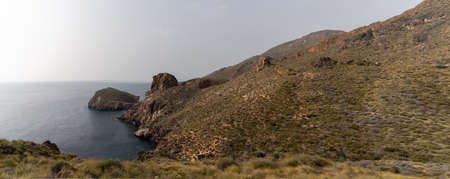 wild mountain and hill landscape on the coast of Murcia with cliffs and small secluded coves under an overcast sky