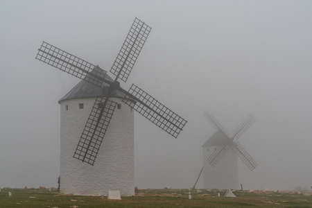 A view of the windmills of Campo de Criptana in La Mancha on a very foggy morning