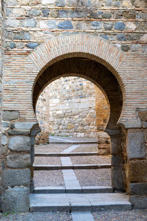 an Arabic horseshoe arch entrance through the old city wall in Toledo Stock Photo