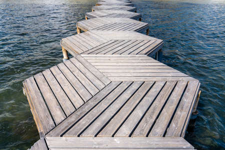 A close up low angle abstract view of a wooden boardwalk and pier leading out into the ocean