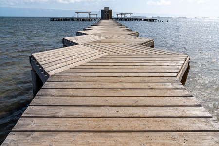 A wooden boardwalk leading out into the ocean to a public bath installation