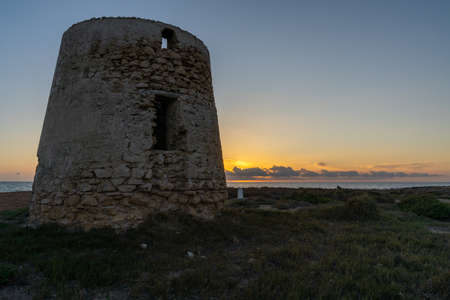 A view of old windmill ruins on the coast of Murcia at sunset