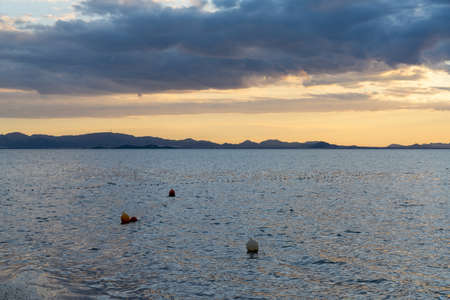 View of calm ocean waters under an expressive sky at sunset with mountain silhouette in the background and buoys in the foreground