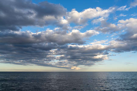 lA andscape of calm dark blue ocean water under an expressive sky with clouds Reklamní fotografie