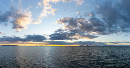 View of calm ocean waters under an expressive sky at sunset with mountain silhouette in the background Reklamní fotografie