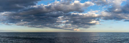A panorama landscape of calm dark blue ocean water under an expressive sky with clouds