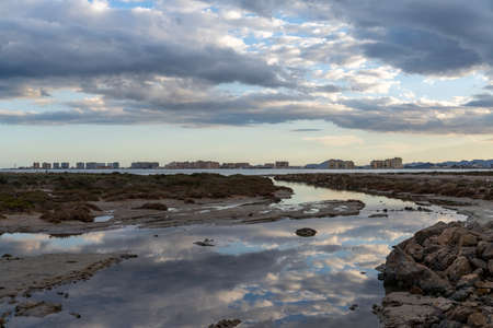 Scenic reflections of sky in rocky tidal pools with the hotels of La Manga del Mar Menor in the background