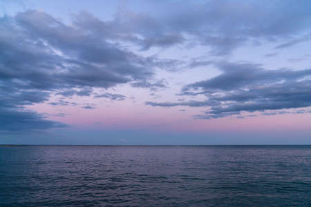 A background landscape of calm dark blue ocean water under an expressive sky with clouds at sunset Reklamní fotografie