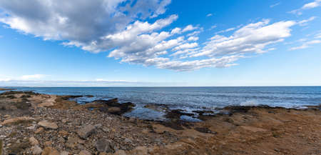 A panorama landscape of a rocky Mediterranean beach at low tide under an expressive sky