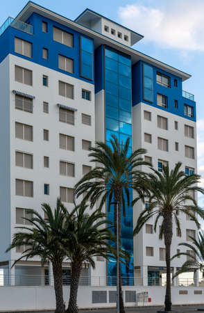 A modern blue and white multi-storey hotel building with palm trees in the foreground