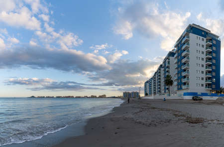 Endless empty beach and hotels in La Manga del Mar Menor in Murcia under an expressive evening sky
