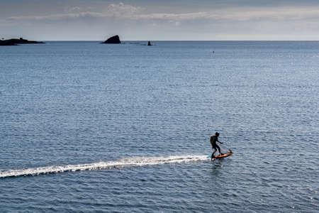 Cadaques, Spain - 13 March, 2021: man riding a motorized surfboard in the Mediterranean Sea near Cadaques 新闻类图片