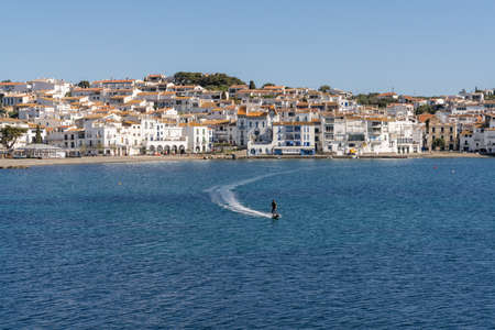 Cadaques, Spain - 13 March, 2021: man on a motorized surfboard in the Meditarranean Sea with Cadaques village and bay behind 新闻类图片