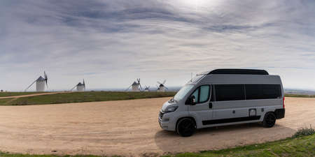 Campo de Criptana, Spain - 26 February, 2021: a gray camper van parked next to the whitewashed windmills of La Mancha in central Spain