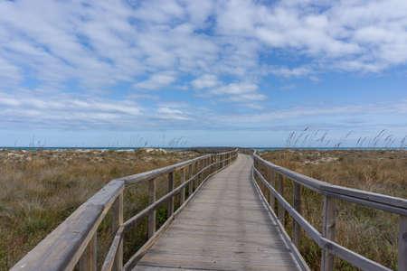 A wooden boardwalk leading through coastal marshlands and sand dunes Stock Photo
