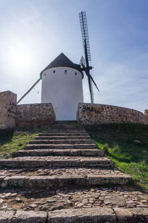 A whitewashed historic windmill typical of the La Mancha region of central Spain under a blue sky